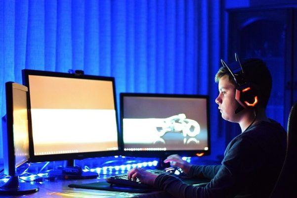 ילד יושב מול מסכי מחשב